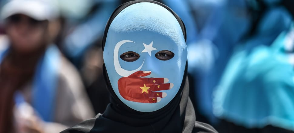 A woman protests the Chinese treatment of it's Uighur population. Photo: Getty.