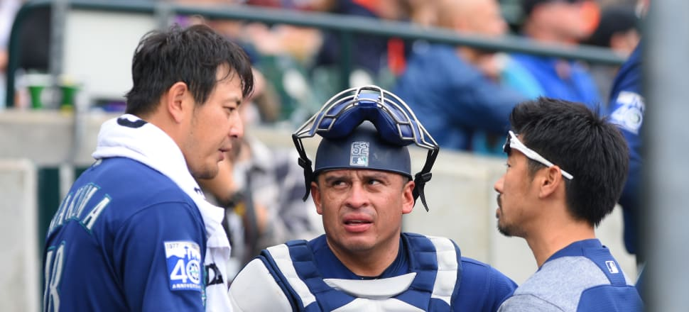 Hisashi Iwakuma and Carlos Ruiz of the Seattle Mariners talk to each other through an interpreter during a Major League Baseball innings. Photo: Getty Images