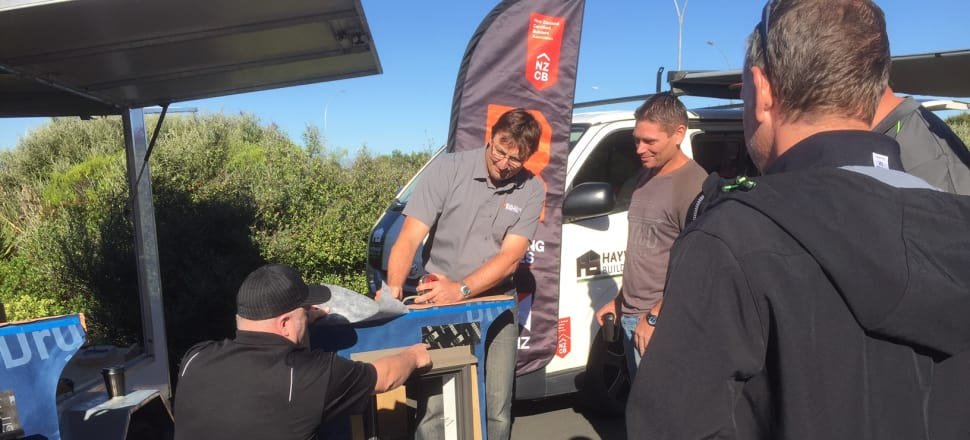 Builder Mike Hayward (left) gets a skills update from demonstrator Jason McClintock (wearing glasses) on a building site in Hamilton with the travelling home improvement trailer, Photo: NZCB