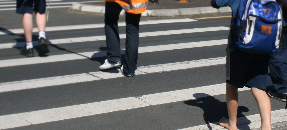 A shoe-less child crosses a patrolled school crossing in Auckland. Photo by Lynn Grieveson for Newsroom.