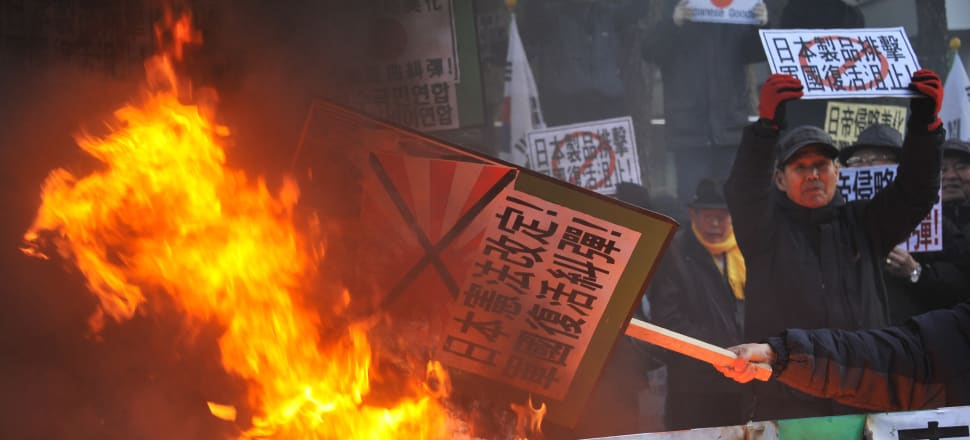 South Korean protestors set fire to images of Japanese Prime Minster Shinzo Abe in protest at his visit to a shrine that honours war criminals, as well as fallen soldiers. Photo: Getty.