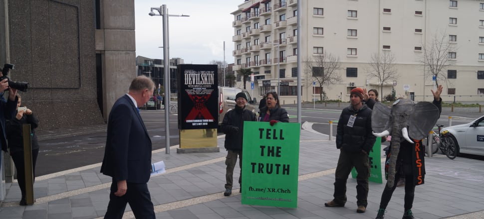 National MP Nick Smith walks by Extinction Rebellion Ōtautahi protesters outside the party's annual conference in Christchurch. Photo: Sam Sachdeva.