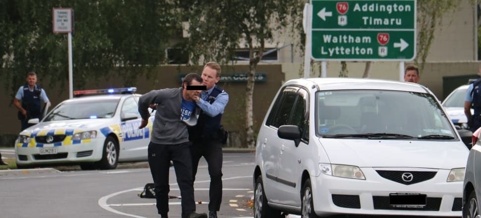 A man is apprehended by police in the wake of mass shootings at two mosques in Christchurch. Photo: David Williams