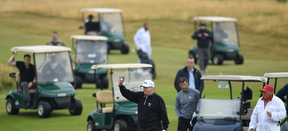 Trump waves while playing a round of golf at Trump Turnberry Luxury Collection Resort in Scotland. Photo: Getty Images