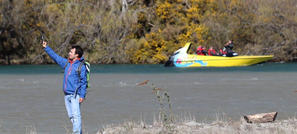 A tourist captures the moment on the shores of the Kawarau River, near Queenstown. Photo: David Williams