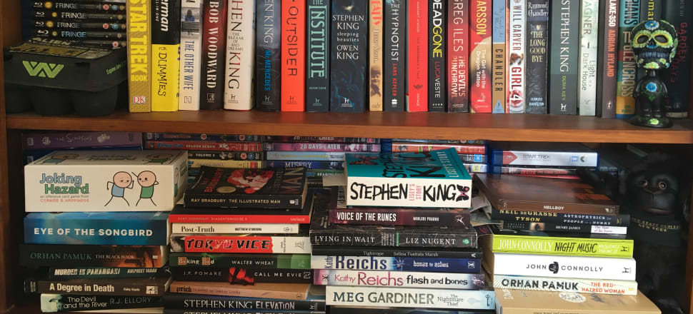 Stephen King, junk blockbusters, and a day of the dead bobblehead from Mexico in a bookshelf in the Christchurch home of crime novelist Paul Cleave.