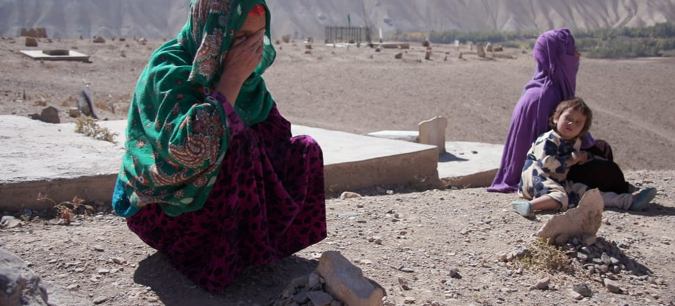 Two of the mothers of the seven children who died in the blast on April, 2014, Baskul and Tohira, with one of Tohira's other children, at the cemetery where the children are buried. Photo: Phil Johnson, Stuff Circuit