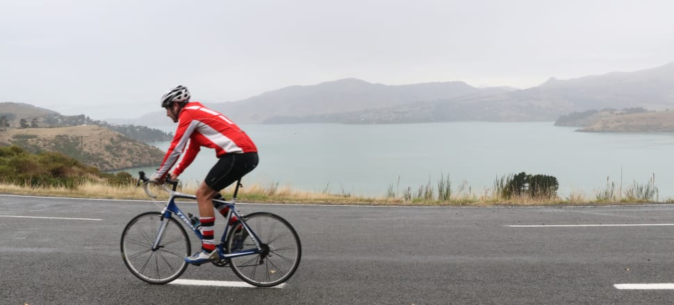 A cyclists stretches their legs, and the definition of neighbourhood, near Rāpaki. Photo: David Williams