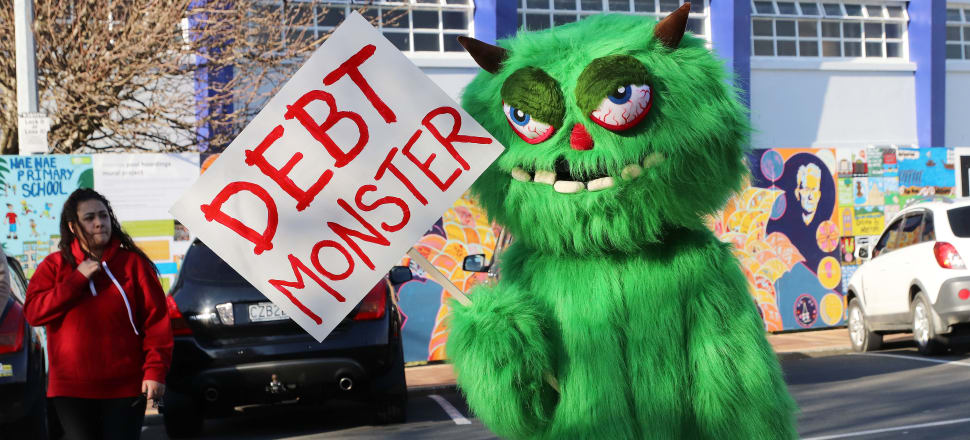 Taxpayers Union debt monster mascot attempting to photobomb Jacinda Ardern in Naenae for infrastructure spending announcement. photo: Lynn Grieveson