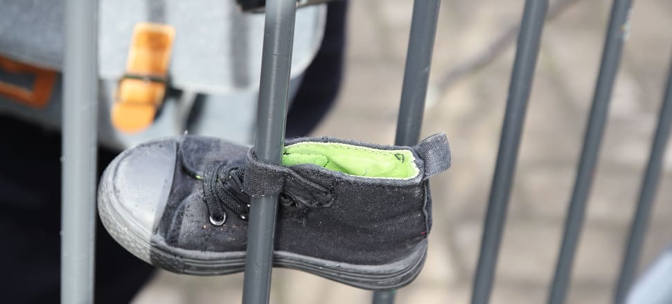 A child's shoe is attached to the barricade for a Hands Off Our Tamariki protest at Parliament. Photo: Lynn Grieveson.