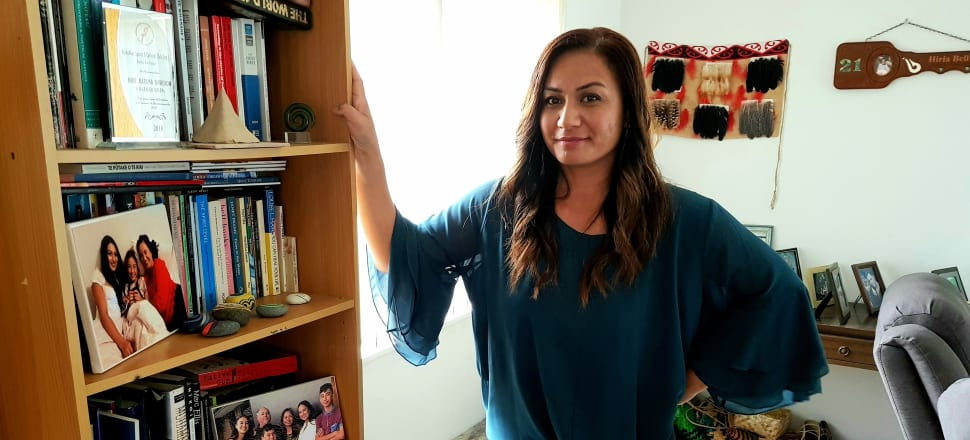 Modelling her new bougie haircut, Green Party co-leader Marama Davidson poses by a bookshelf in her Auckland home. Titles include poetry by Hone Tuwhare and Karlo Mila, fiction by Patricia Grace and Albert Wendt, two biographies of Muhammad Ali, and something called You Can Heal Your Life.