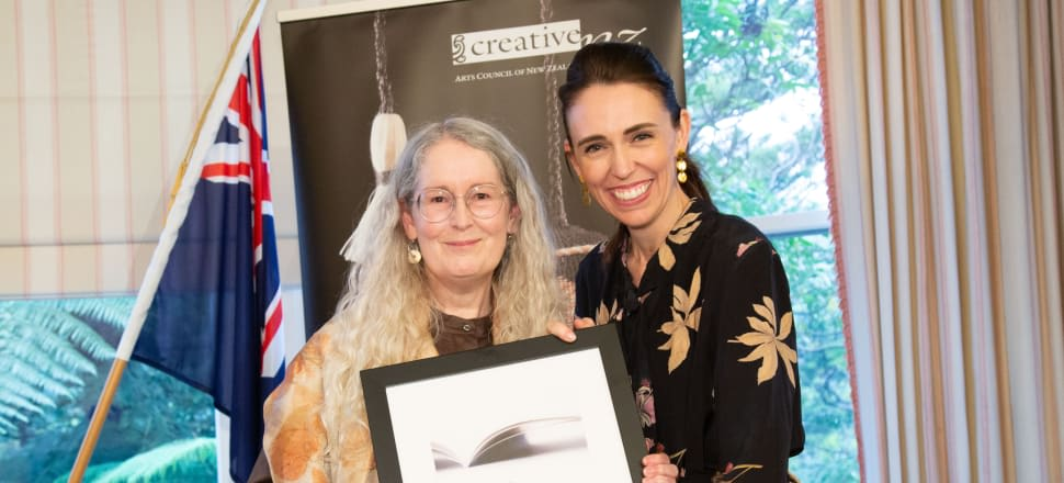 Elizabeth Knox, author of The Absolute Book, receives a cheque from Jacinda Ardern as the winner of the 2019 Prime Minister's Literary Award.