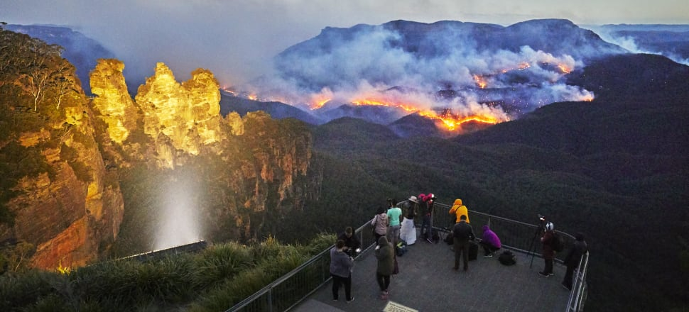 Tourists photograph a bushfire in the Blue Mountains National Park in Australia. The tourism sector are bound to undergo changes thanks to climate change. Photo: Getty Images