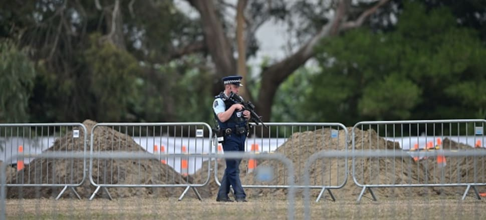 An armed police officer patrols gravesites for victims of the Christchurch terrorism attack. Photo: Getty Images