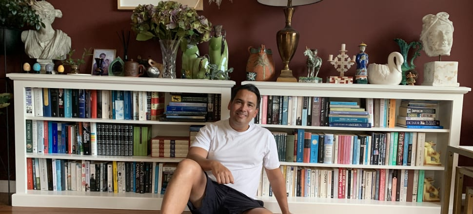 National Party leader Simon Bridges in casual repose in front of his bookcase at his Tauranga home. Titles include Last Days of the Reich, biographies of John Howard and Phil Collins, a collection of essays by CK Stead, and a book about how parliament works.