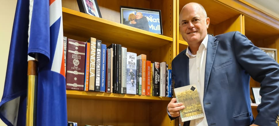 """This week's bookshelf star is National Party leader Todd Muller, who just happens to be posing with a book of poetry by Allen Curnow. Muller quoted from a famous poem by Curnow when he rolled Simon Bridges to win the leadership, and laid out his vision for a proud, confident New Zealand: """"Not I, some child, born in a marvelous year/ Will learn the trick of standing upright here."""" The poem is about children in awe of a moa skeleton at the Canterbury museum. Curnow describes the moa as an """"interesting failure""""."""