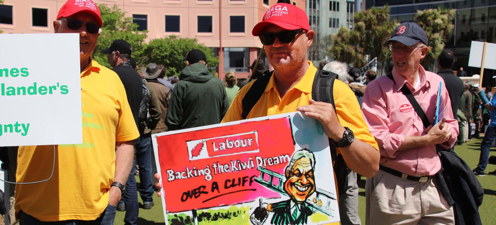 Accomplice or opponent? Men in MAGA (Make Ardern Go Away') hats at last year's '50 Shades of Green' farmers' protest hold a poster picturing a grinning Winston Peters walking away from a defaced Labour poster. Photo: Lynn Grieveson