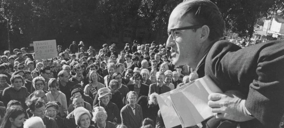 Karl Stead addresses an anti-Vietnam War rally in Myers Park, Auckland, 1968. Note the hipster smoking a long-stemmed pipe, several amused grannies, and a placard reading YANKEE FASCISTS GO HOME.