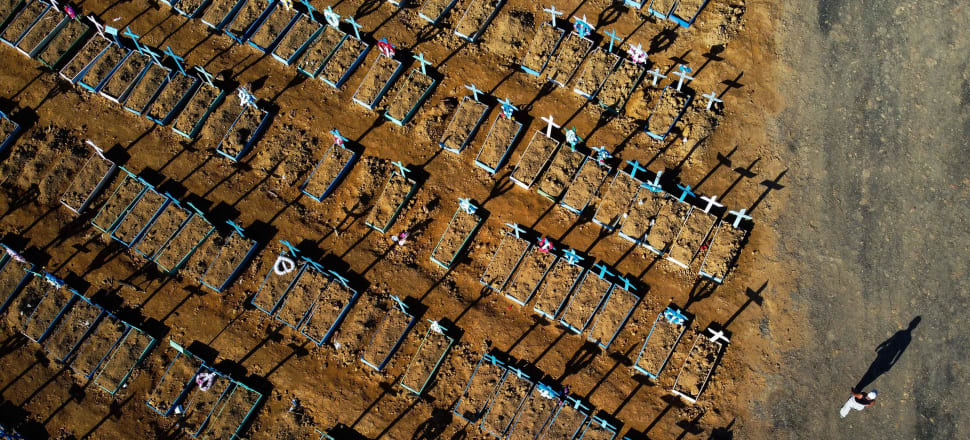Aerial view showing a man walking past graves in the Nossa Senhora Aparecida cemetery in Manaus. Photo: Getty.