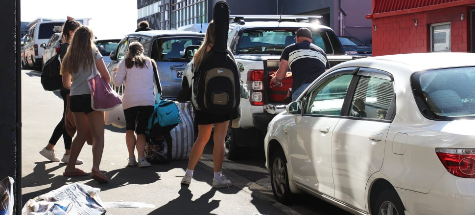 Students evacuating Wellington student residences pack suitcases into a car as they prepare to leave the city. Photo: Lynn Grieveson